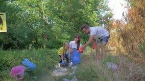 Stoppa den plast- unga mamman och farsan med små dotteromsorger om ekologinaturen och mot efterkrav polyetylenkull i avfall stock video