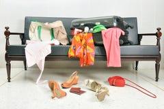 Stoppa och beklär resväskan spridd i en soffa Arkivbilder