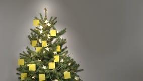 Stoppa rörelse av 25 som det gula mellanrumet stolpe-honom noterar själv-avslutning ett julträd stock video