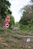 Stoppa tecken med korset vid den raka järnvägen Royaltyfri Foto