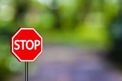 Stoppa teckentrafiktecken, rött stopptecken på naturbackg för blå gräsplan Arkivbild