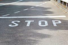 Stoppa tecknet på asfalt Arkivfoto