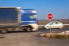 Stoppa tecknet på tvärgator lantlig väg Gå ut på huvudvägen Huvudvägen farlig väg Stopp för trafiktecken Arkivbild
