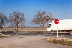 Stoppa tecknet på tvärgator lantlig väg Gå ut på huvudvägen Huvudvägen farlig väg Stopp för trafiktecken Arkivfoto