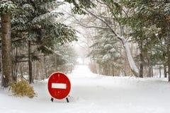 Stoppa tecknet på vägen för vinterlandsskogen under snöfall Royaltyfri Foto