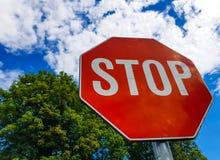 Stoppa trafiktecknet på solig dag, härlig blå himmel med vita moln Arkivfoton