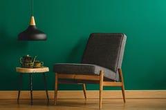 Stoppad stol vid den gröna väggen royaltyfri bild
