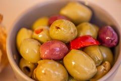 Stoppade oliv, röd peppar och kryddor av örter arkivbild