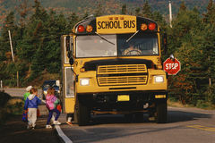 Stopped School Bus. Children boarding a yellow school bus, New England Royalty Free Stock Photography