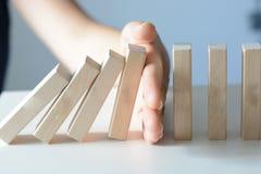 Stoppen des Domino-Effekt-Konzeptes mit einer Geschäftslösung lizenzfreie stockfotos