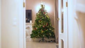 Stoppen Sie Bewegung Ohne die Leute, die einem künstlichen Weihnachtsbaum, erscheinen allmählich Bälle angebracht werden, Girland Stockfoto