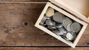 Stoppen Sie Bewegungsgesamtlänge Silbermünzen thailändischen Baht, der des hölzernen Kastens des Spielzeugs auf wwod Tabelle, Dra stock video footage