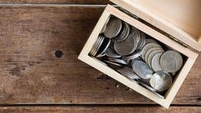 Stoppen Sie Bewegungsgesamtlänge Silbermünzen thailändischen Baht, der in hölzernen Kasten des Spielzeugs auf wwod Tabelle, Drauf stock video footage