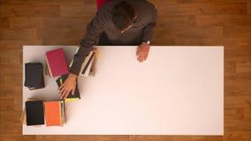 Stoppen Sie Bewegungsspitze schoss vom Mann, der seine Hand über den verschwindenen Büchern auf der Tabelle bewegt, die sie auf L stock video