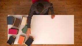 Stoppen Sie Bewegungsspitze schoss vom Mann, der seine Hand über den verschwindenen Büchern auf der Tabelle bewegt, die sie auf T stock footage