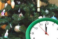 Stoppen Sie das Zeigen von zwölf Stunden und von gekleidetem oben Weihnachtsbaum ab Stockfotos