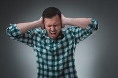 Stoppen Sie diese lauten Geräusche! Stehender einfacher junger Mann traurig und deprimiertes leidendes Sorgen- und Schmerzschreie Stockfotografie