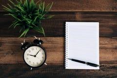 Stoppen Sie, Grünpflanze, Stift ab und löschen Sie Notizbuch auf Holztisch Stockfotografie
