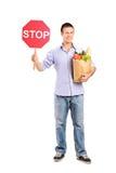 Stoppen Sie und kaufen Sie hier Ganzaufnahme eines Mannes, der ein pape hält Lizenzfreies Stockfoto