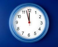 Stoppen Sie ungefähr ab, um Mitternacht oder Mittag auf blauem Hintergrund zu schlagen Stockfotografie