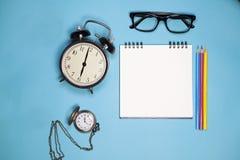 Stoppen Sie, weißes Notizbuch auf Frühlingen, Gläser und farbige Bleistifte auf einem blauen Hintergrund ab Lizenzfreies Stockbild