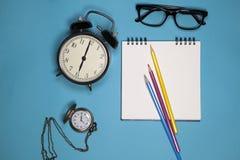 Stoppen Sie, weißes Notizbuch auf Frühlingen, Gläser und farbige Bleistifte auf einem blauen Hintergrund ab Stockbild