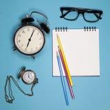 Stoppen Sie, weißes Notizbuch auf Frühlingen, Gläser und farbige Bleistifte auf einem blauen Hintergrund ab Lizenzfreie Stockfotografie