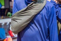 Stoppet som blöder den högra armen vid triangeltyg, improviserar Arkivfoto