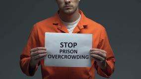 Stoppfängelse som överbefolkar uttryck på papp i händer av den Caucasian fången stock video