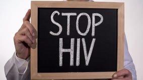 StoppHIV-text på svart tavla i doktorshänder, HJÄLPMEDEL medvetenhet, sjukdomförhindrande royaltyfri fotografi