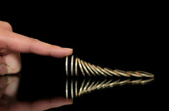 Stopping the fall. Finger is stopping the fall of coins Royalty Free Stock Photos