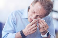 Cheerless unhappy man wiping his eyes. Stopping tears. Cheerless unhappy adult man holding a paper tissue and wiping his eyes while having an allergic reaction Royalty Free Stock Photos