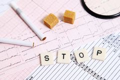 Stopping vices and heart disease. Several letters put on an electrocardiogram for an alarm message stock image