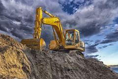 A stopping yellow excavator. At an incredibly beautiful sunset Stock Photography
