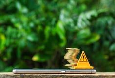stopptecknet och mynt är riskabla på den smarta telefonen eller mobiltelefonen på nat Arkivfoto