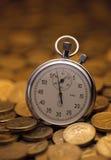 Stoppuhr an gehäuft von den Goldmünzen Stockfoto