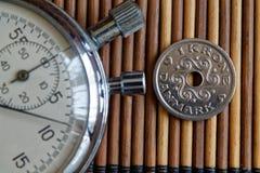 Stoppuhr und Münze mit einer Bezeichnung von Cents mit 1 Dänenkronen auf Holztischhintergrund Stockbilder