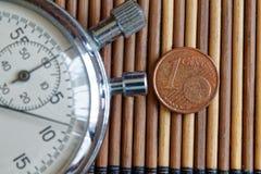 Stoppuhr und Münze mit einer Bezeichnung von 1 Eurocent auf Holztischhintergrund Lizenzfreies Stockbild