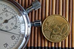 Stoppuhr und Münze mit einer Bezeichnung von 50 Eurocents auf Holztischhintergrund Stockfotos