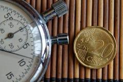Stoppuhr und Münze mit einer Bezeichnung von 20 Eurocents auf Holztischhintergrund Stockbild