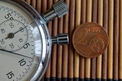 Stoppur och mynt med en valör av 2 eurocent på trätabellbakgrund Arkivfoto
