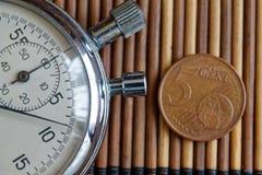 Stoppur och mynt med en valör av 5 eurocent på trätabellbakgrund Royaltyfri Bild