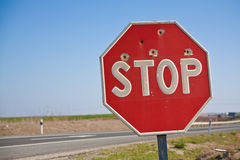 Stopsign with bullet hole. On highway Stock Image