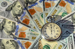 Stopwatch on the background of dollar bills (time - money, incom Stock Photography