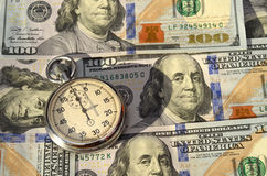 Stopwatch on the background of dollar bills (time - money, incom Royalty Free Stock Photography