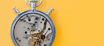 Stopwatch chronometer mechanism cogs gears wheels connection concept. Clock transmission macro view. Shallow depth of. Field, copy space. Yellow background Royalty Free Stock Photography