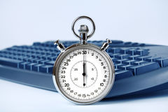 Stopwatch and computer keyboard. Royalty Free Stock Image