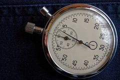 Stopwatch on dark blue jeans background, value measure time, old clock arrow minute and second accuracy timer record Stock Image