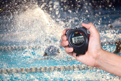 Stopwatch holding on hand with competitions. Stopwatch holding on hand with competitions of swimming background Stock Photos