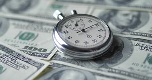 The stopwatch lies on the dollars. Time is money concept.